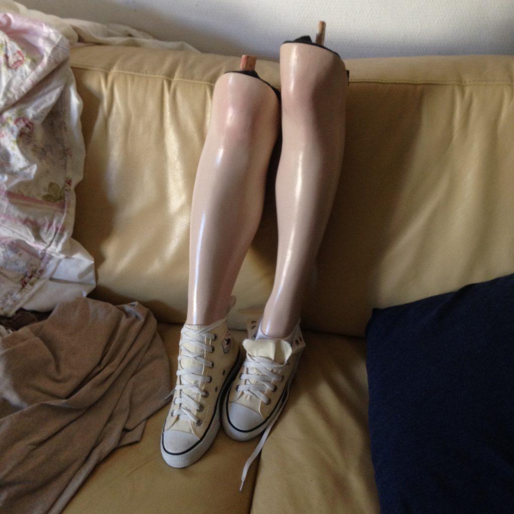 Dwie nogi od manekinów stojące na kanapie. Nogi w kolorze cielistym, ścięte powyżej kolan. Na stopach dwa trampki w kolorze jasnym żółtym, z białymi noskami. Obok na kanapie rozrzucone luźne materiały i ciemna poduszka.