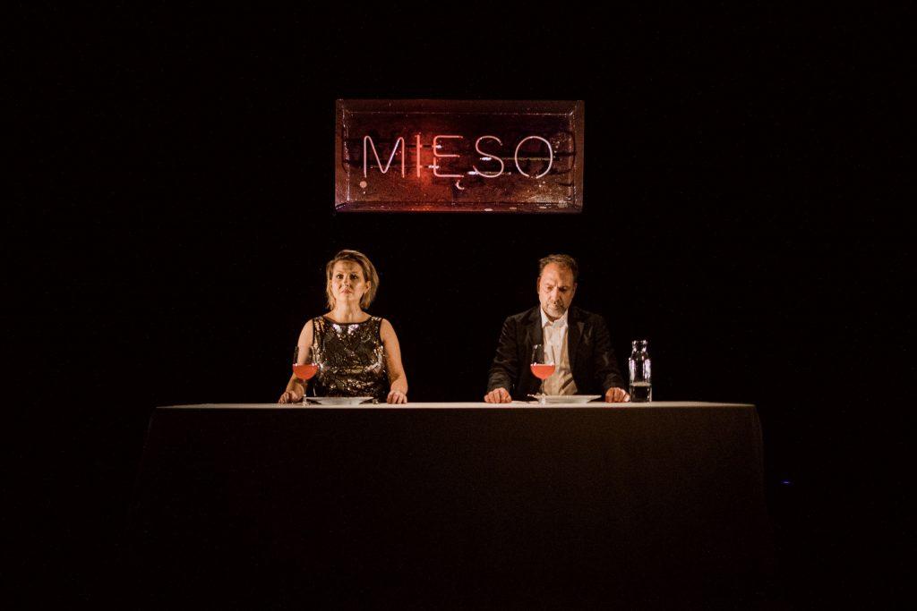 Kobieta i mężczyzna siedzą za stołem. Stół nakryty prostym obrusem. Przed osobami stoją talerze i kieliszki. Za nimi wisi neon z napisem
