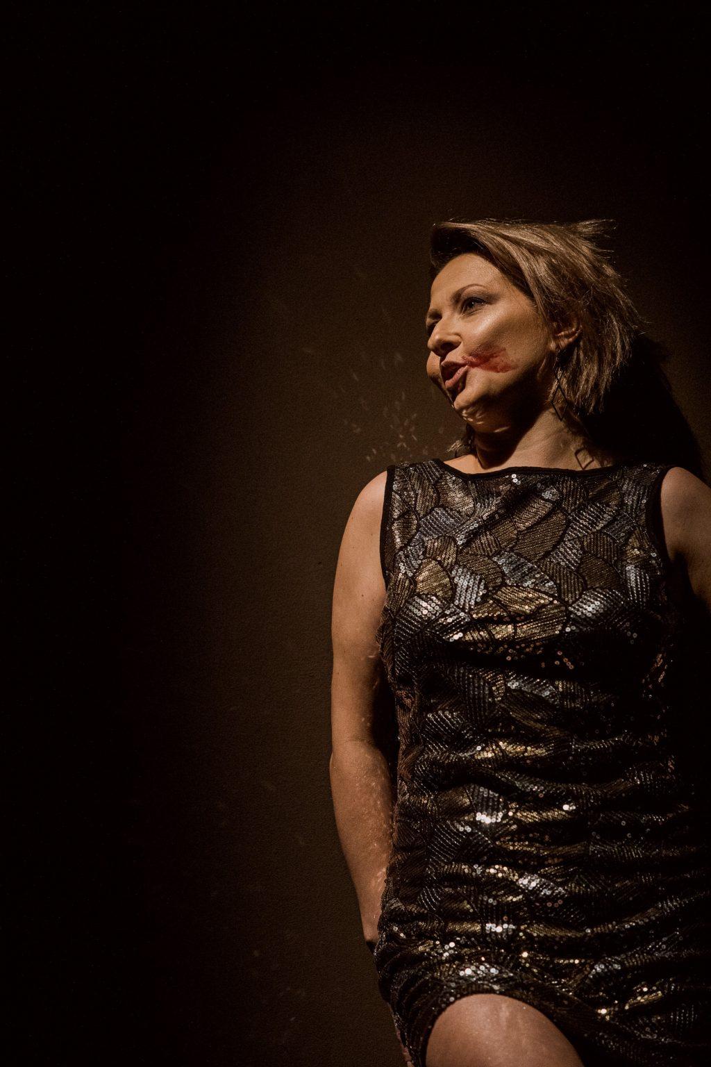 Kobieta w eleganckiej, obcisłej sukience. Stoi oparta o ścianę. Patrzy e lewą stronę kadru. Na twarzy ma rozmazaną czerwoną szminkę.