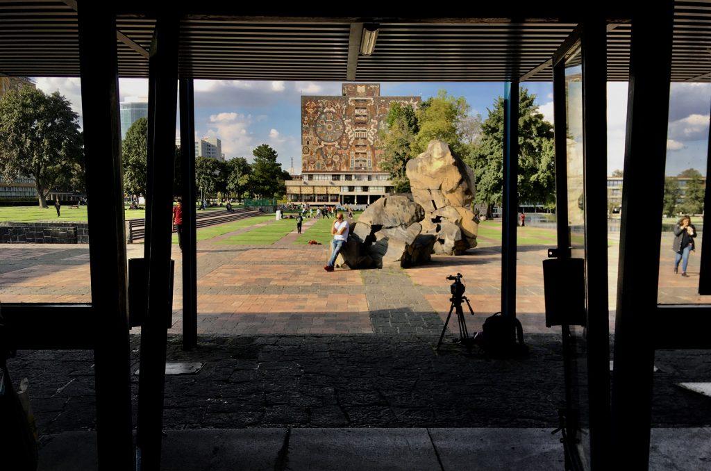 Na zdjęciu na plac miejski widziany z wewnątrz, zza otwartych drzwi wejściowych budynku. Na środku placu stoją dwie kamienne rzeźby. O jedną z rzeźb opiera się tyłem mężczyzna.W tle widać budynek z mozaiką o tematyce mitów meksykańskich.