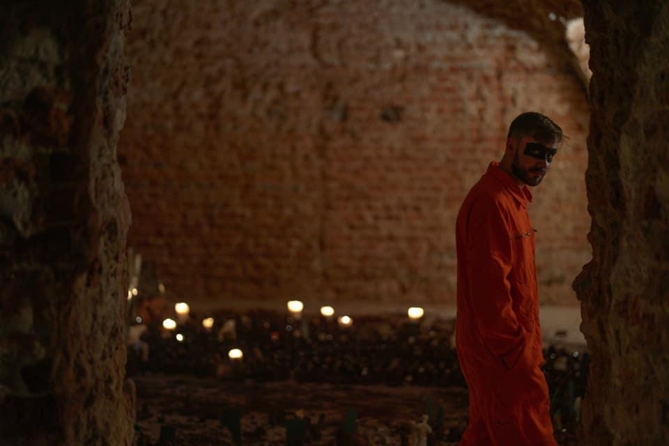 Piwniczna sala o ceglanych ścianach. Po prawej stronie kadru idący, młody, brodaty mężczyzna w pomarańczowym więziennym kombinezonie, z czarnym paskiem namalowanym w poprzek oczu. Patrzy w naszą stronę i przechodzi w poprzek kadru. Na podłodze sali setki glinianych figurek z lusterkami, odbijającymi bliki światła.