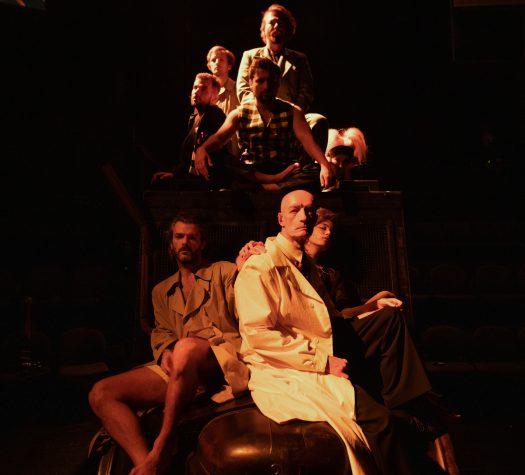Grupa siedzących ludzi, częściowo oświetleni miękkim, złoto-czerwonym światłem. Postacie na pierwszym planie bardziej wyraźne, dwóch mężczyzn i kobieta, która trzyma rękę na ramieniu jednego z nich. Ponad nimi na podeście siedzi druga grupa mężczyzn, mniej wyraźna.