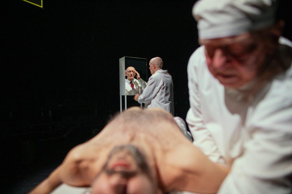 Widok w dwóch planach. Z przodu rozmazana scena, mężczyzna w fartuchu lekarskim, pochyla się nad leżącym, nagim mężczyzną pokazanym w skrócie perspektywicznym, twarz najbliżej do przodu kadru. W tle wyraźnie widoczny mężczyzna w fartuchu, stoi i przegląda się w lustrzanych drzwiach szafki na wysokich nogach
