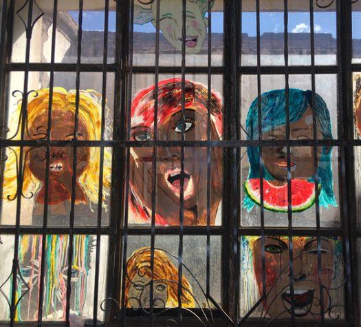 Zbliżenie na zakratowane okno, widziane z wnętrza budynku. Okno jest podzielone na kwadraty - cztery w pionie, trzy w poziomie. Na szybach okna namalowane kolorowe twarze.