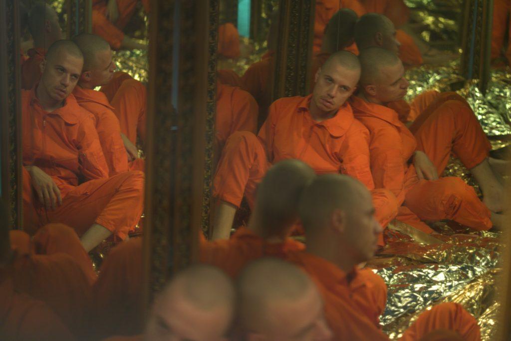 Ciemna, piwniczna, półkoliście sklepiona, ceglana sala. Pod ścianą dwóch mężczyzn w pomarańczowych więziennych kombinezonach z rękami wyciągniętymi przed siebie, oboje w identycznym geście. Na twarzach na wysokości oczu mają namalowane czarne, szerokie paski. Na podłodze sali setki glinianych figurek z powtykanymi w nie drobnymi odłamkami lusterek i zapalonych świec.