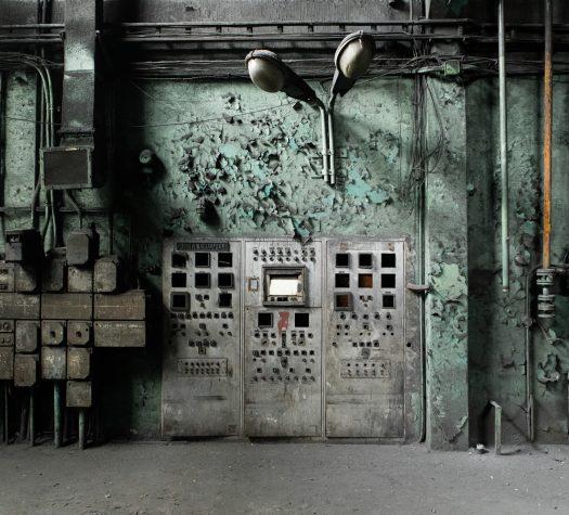 Ściana w pomieszczeniu fabrycznym. Na ścianie stare skrzynki prądowe, urządzenia elektryczne, zniszczone. Wszystko pokrywa szary kurz, na ścianie odchodzi płatami farba. Ogólne wrażenie opuszczonego budynku.