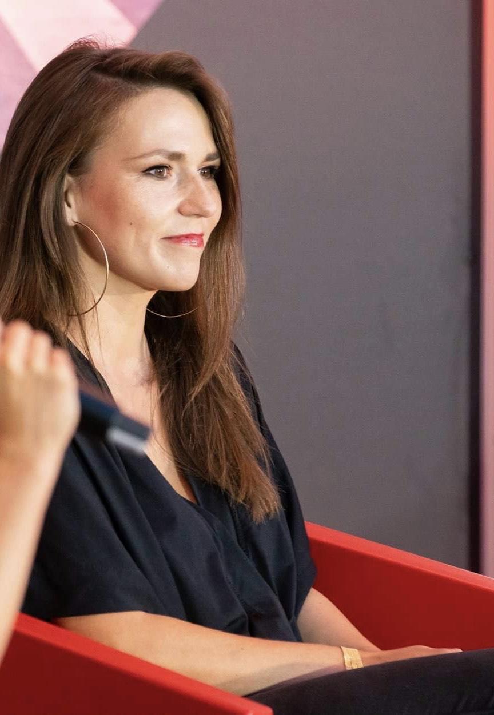 Uśmiechnięta młoda kobieta widziana z profilu.